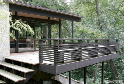 A charcoal deck railing with horizontal planks perfectly complements the striking architecture of this modern home.
