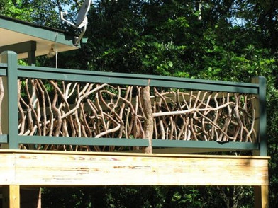An arboreal green rail is finished with 'cracked ice' fencing, made from real branches and logs for a natural look.