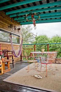 A whimsical boho outdoor space features quirky pops of color, with a turquoise railing to match the roof's wood beams.