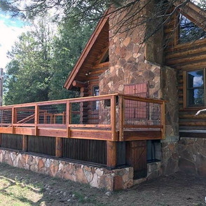 A log cabin deck blends in with its surroundings, featuring a stained wood frame and medium-square hog wire fence.