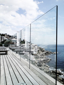 A washed gray deck is kicked up a notch with luxury glass balustrades, making it easy to enjoy the ocean views.