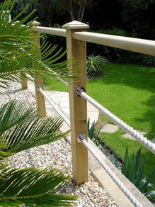A cottage-style pale wood railing is accented with a simple rope fence.