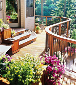 A curved railing brings a touch of whimsicality to this modern, orange wood deck.