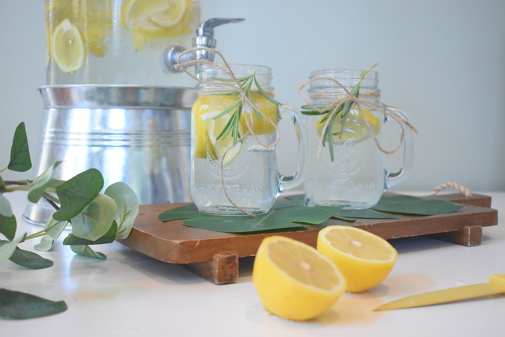 Mason jars with water and lemon slices sit on a counter
