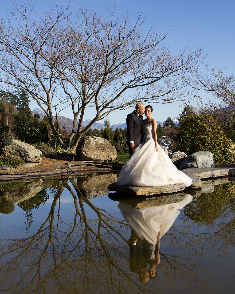 A Bride and Groom kissing with water reflection