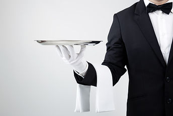 Waiter holding empty silver tray over gr