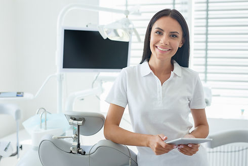 cheerful dentist in coat using tablet in