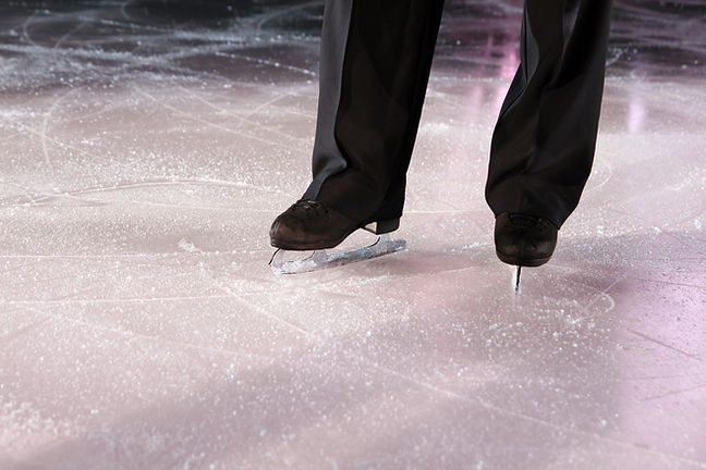 The man figure skater in ice stadium.jpg