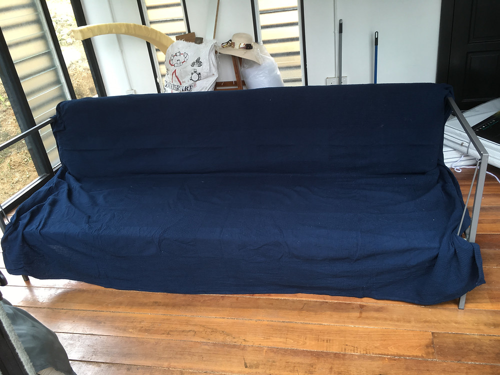 Sofa frame covered with bedspread