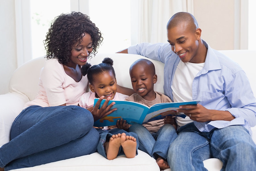 Happy family on the couch reading storybook at home in the living room.jpg