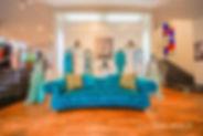 Innenansicht Ilse-Moden, blaues Sofa mit Thomas Rath Bild darüber, links und rechts befinden sich schwarze Treppen.