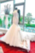 Schaufensterpuppe ohne Kopf mit Brautkleid auf einem weissem Podest.