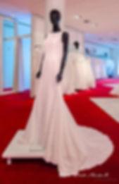 Innenaufnahme mit schwarzer Schaufensterpuppe und Brautkleid auf Podest auf rotem Teppich bei Ilse-Moden.