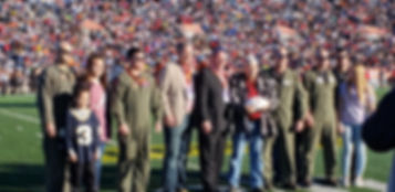 Lettermen of the USA Board Members Ward Murphy and Phil Quigley present autographed University of Alabama football to wounded Vietnam Veteran, Lance Cpl Donnie Carter, USMC (RET) during the 70th Annual Reese's Senior Bowl in Mobile, AL on January 26, 2019. Pictured also are the pilots who provided the national anthem flyover. Pilots pictured are stationed out of Pensacola, FL NAS