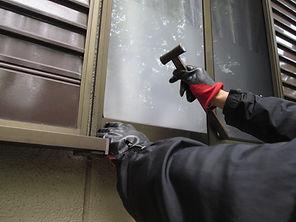 窓を割ろうとする人