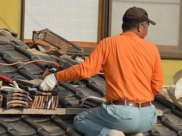 屋根で作業している男性