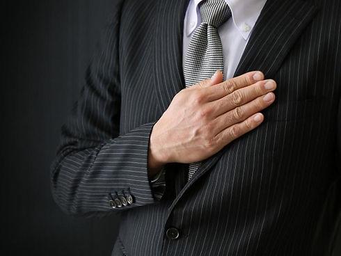 スーツの胸に手を置く