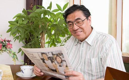 新聞読んでる男性