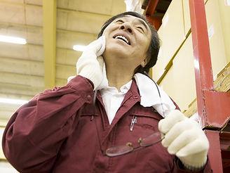 汗をタオルで拭いている作業員