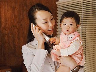 電話する子供を抱く女性