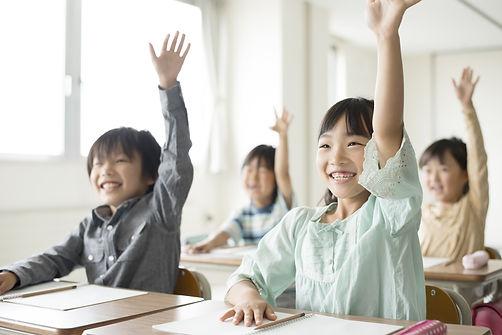 教室で手をあげる小学生