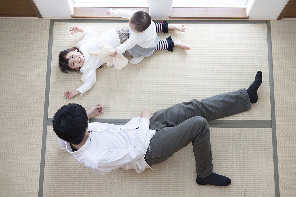 畳の上に寝転ぶ家族