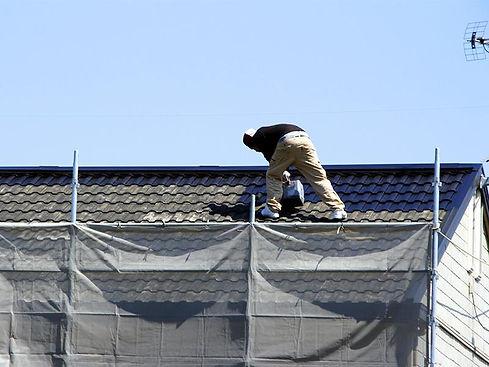 屋根を塗装する男性