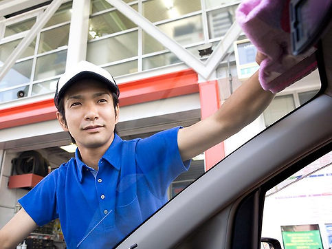 車の窓を拭いている男性