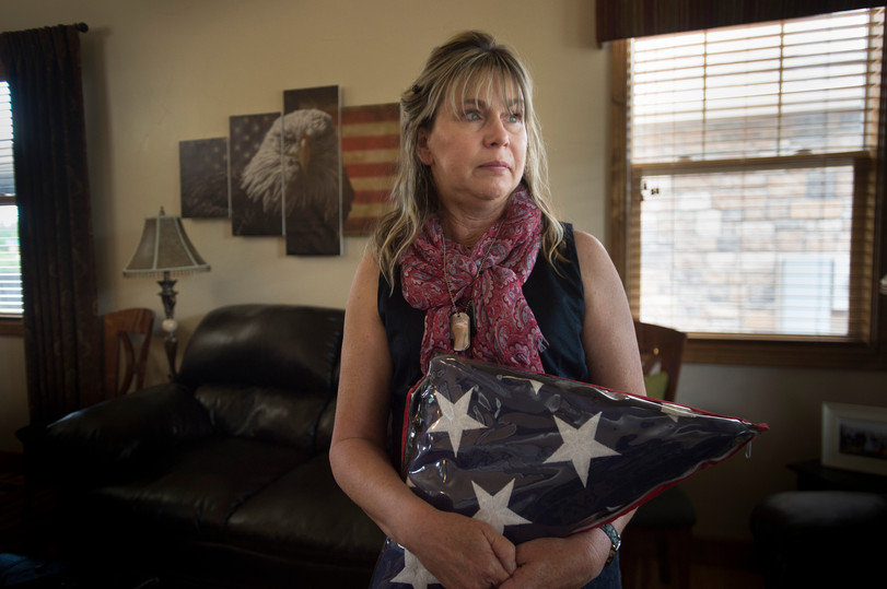 Pam Birdwell poses for a portrait holding the flag that was draped over her son Chris' casket after he returned from Afghanistan at her family's Windsor home on Thursday, May 24, 2018. Staff Sergeant Chris Birdwell was killed during his third tour in 2012.