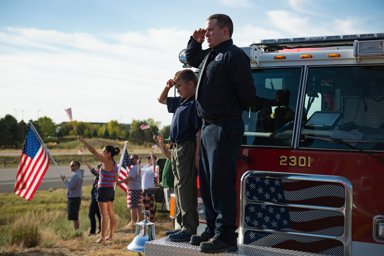 Eaton firefighter Chris Vilkaitis salutes with his son, Jack, 10, as veterans participating in Honor Flight Northern Colorado drive by on I-25 in Loveland on Sunday, September 9, 2018. Honor Flight Northern Colorado sent one last group of veterans to Washington D.C. to visit war memorials in the nation's capital. AUSTIN HUMPHREYS/THE COLORADOAN