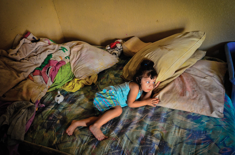 Angelica Cua, 2, rests on the bed she shares with her sister, Gabby Suacedo, 10. The sisters live in a one bedroom home with their mother, Lupe and Angelica's father, Angel. The family moved into the home last November after a six-month stay at the Southside Community Center. AUSTIN HUMPHREYS/THE UNIVERSITY STAR