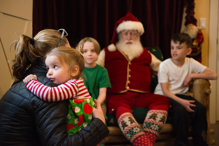 Caroline Housley, 2, holds onto her mother, Kristi, as she visits Rick Price portraying Santa Claus with her brothers Graham and Grady in Old Town Square on Thursday, December 13, 2018. AUSTIN HUMPHREYS/THE COLORADOAN