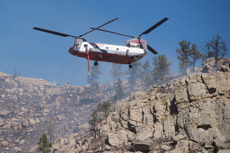 A tandem rotor helicopter prepares to make a water drop as firefighters work to contain a blaze in Poudre Canyon west of Seaman Reservoir on Tuesday, September 12, 2018. AUSTIN HUMPHREYS/THE COLORADOAN