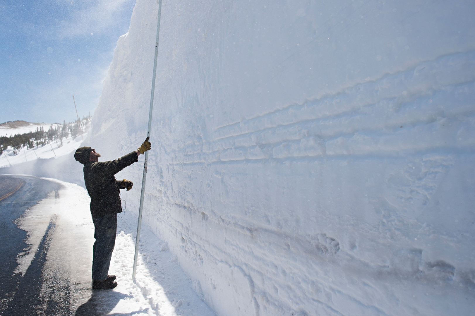 Todd Greer takes a measurement of a 19-foot snow drift on Trail Ridge Road in Rocky Mountain National Park Thursday, May 12, 2016. The road, topping out at over 12,000 feet in elevation, requires a five week snow removal operation to open around Memorial Day each year.