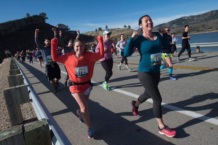 Runners celebrate reaching one mile in the course as they cross Dixon Canyon Dam along Horsetooth Reservoir during the Horsetooth Half Marathon on Saturday, April 14, 2018. AUSTIN HUMPHREYS/THE COLORADOAN