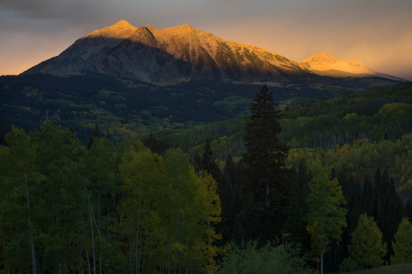 Aspen trees sit in shadow as first light hits the mountains west of Kebler Pass near Crested Butte, Colorado on Friday, September 22, 2017. The aspen trees in the area are reaching their peak fall coloration.
