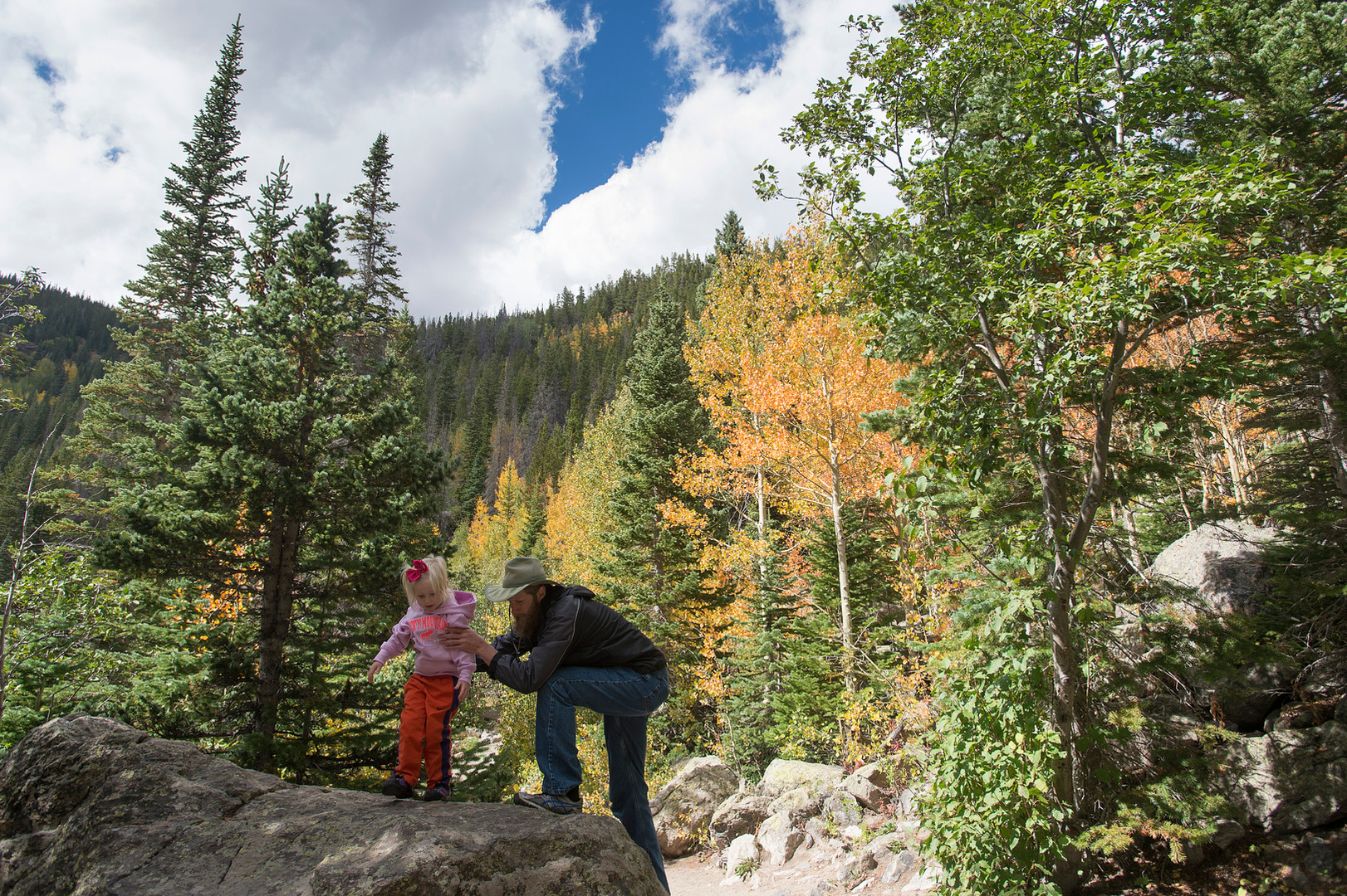 Brian Fletcher and his daughter Adalyn, 3, visiting from Asheville, North Carolina, climb a rock to take a photo surrounded by fall colors on the Bear Lake loop trail in Rocky Mountain National Park Thursday, September 17, 2015.