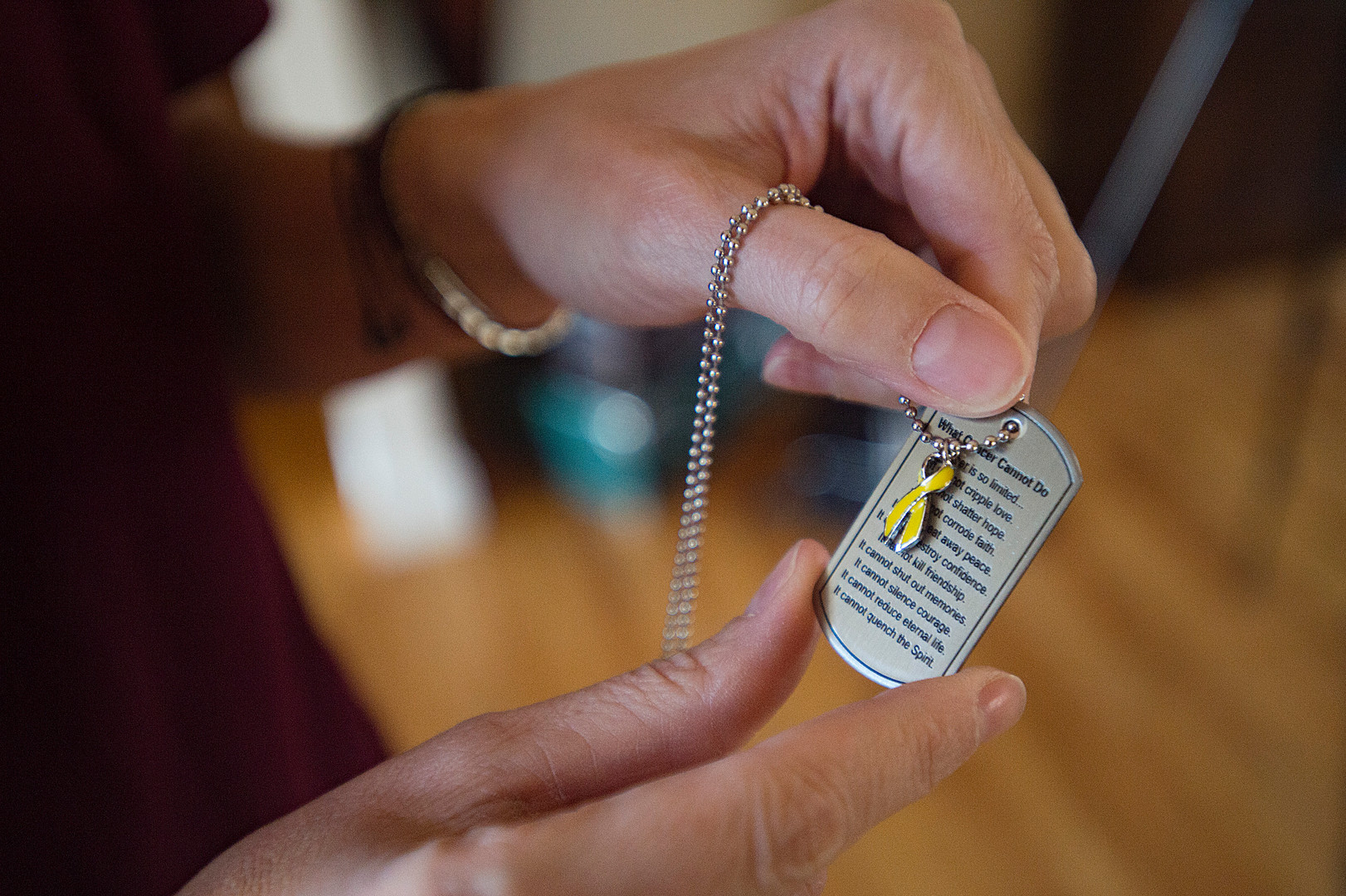 Michelle Edgerley shows off her dog tag with a ribbon symbolizing the fight against childhood cancer at her home in Fort Collins on Tuesday, January 8, 2019. The Edgerley family has been wearing the tags with positive messages on fighting cancer inscribed on them for their son, Carter. AUSTIN HUMPHREYS/THE COLORADOAN