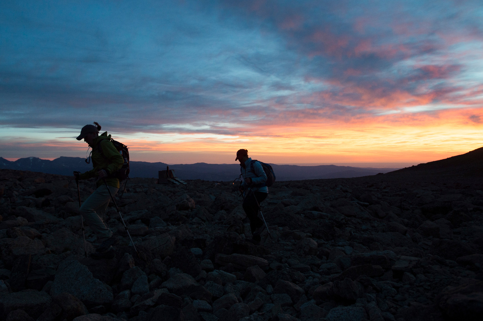 Climbers are silhouetted against a vibrant sunrise in the boulder field of Longs Peak in Rocky Mountain National Park on Friday, July 19, 2017.