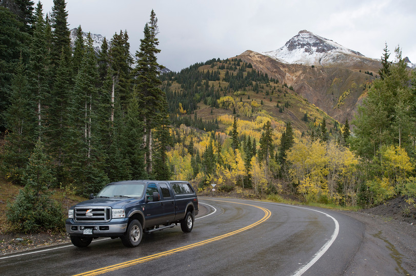 """Snow covers mountain peaks and fall colors show as cars travel along U.S. Highway 50, known as the """"Million Dollar Highway,"""" between the towns of Silverton and Ouray, Colorado on Saturday, September 22, 2017."""