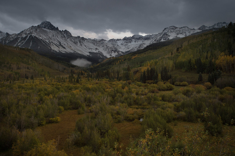 Fresh snow covers Mt. Sneffels, rising 14,157 feet in elevation, above a patch of fall colors near Ridgway, Colorado on Saturday, September 23, 2017.