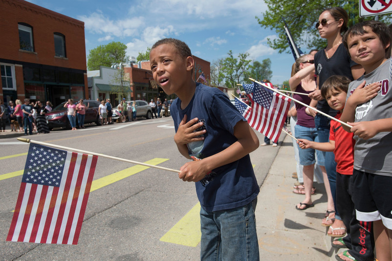 Tayvian Freeman, 9, leans out into the street to get an early glimpse of the funeral procession for fallen U.S. Army Specialist Gabriel Conde as his body travels along Mountain Avenue in Berthoud on Friday, May 11, 2018. AUSTIN HUMPHREYS/THE COLORADOAN