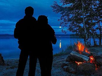 Озеро, тихий вечер, на берегу горит костер. У костра стоят вобнимку парень и девушка.