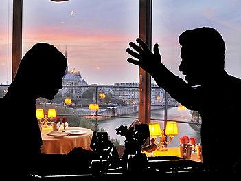 Ресторан. Сквозь большие окна видна панорама вечернего города. На переднем плане парень и девушка. Он что то ей горячо говорит, а она сидит задумавшись и слушает его речь.