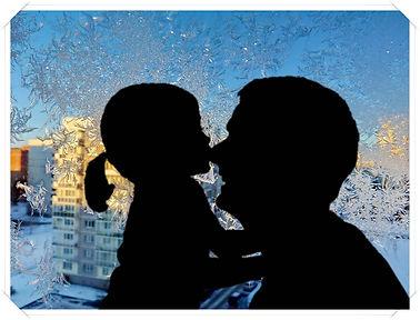 Солнечный зимний день. У покрытого ледяными узорами окна папа обнимает маленькую девочку.