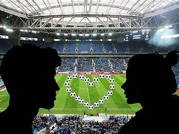 Девушка и пареннь смотрят друг на друга на фоне футбольного поля. На поле мячами выложено сердечко.