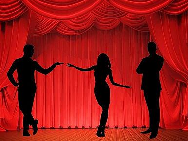 иллюстрация к роману Между Трубадуром и Мачо. На сцене, на фоне алого занавеса стоит иящная девушка и протягивает руки стоящим по бокам мужчинам.