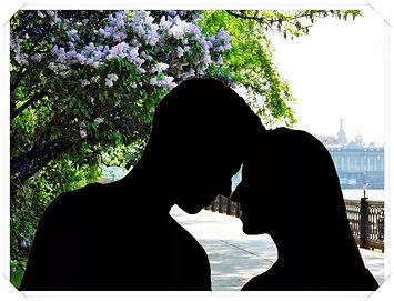 На фоне цветущей сирени склонились друг к другу девушка и парень