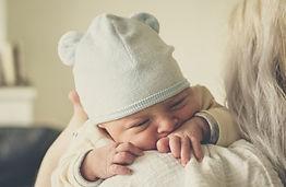 béb qui dort, avec un bonnet blanc sur la tête