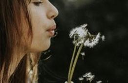 femme soufflant dans unefleur de pissenlit en graines